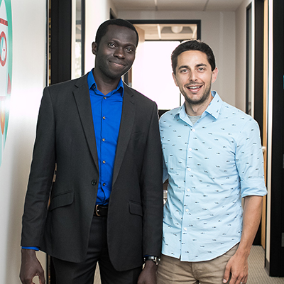 two men standing and smiling