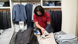 man with long har stacks clothes in store