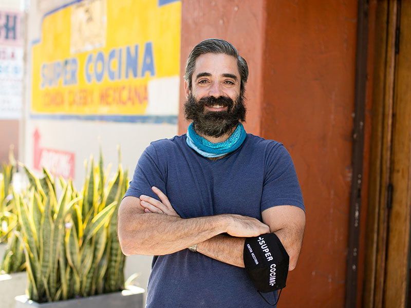 Man With Beard In Front Of San Diego Restaurant With Arms Folded