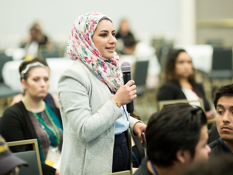 young woman standing in crowd and speaking into mic