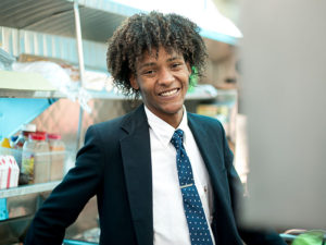 young man in suit smiles into camera