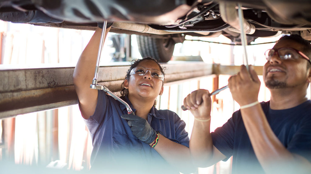 young woman and man in goggles working under car
