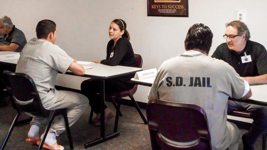Two male inmates site at table talking to employers