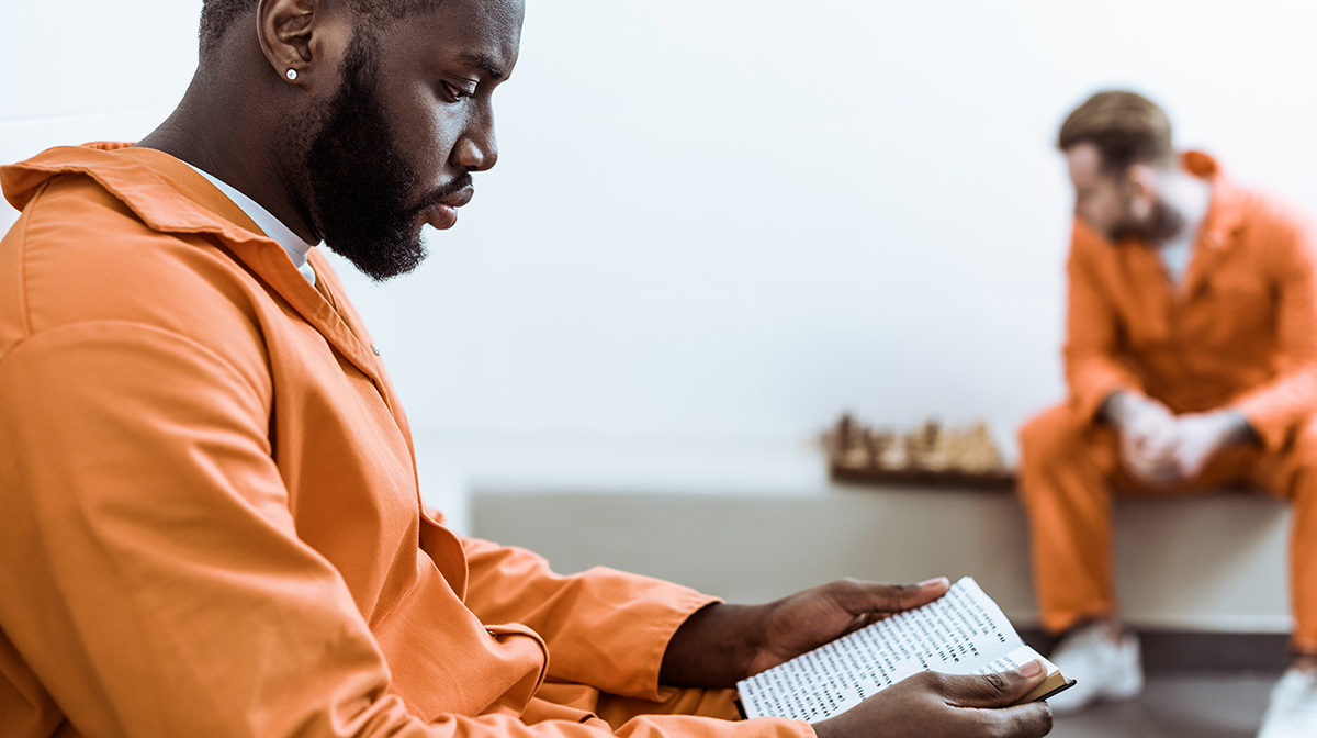 Side View Of African American Prisoner Reading Book