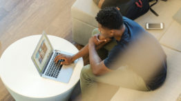 Aerial shot of man sitting on coach looking at laptop on coffee table