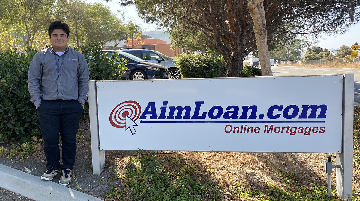 High school boy stands in front of AimLoan.com sign