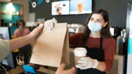 Female Barista Giving Parcel And Coffee To Customer