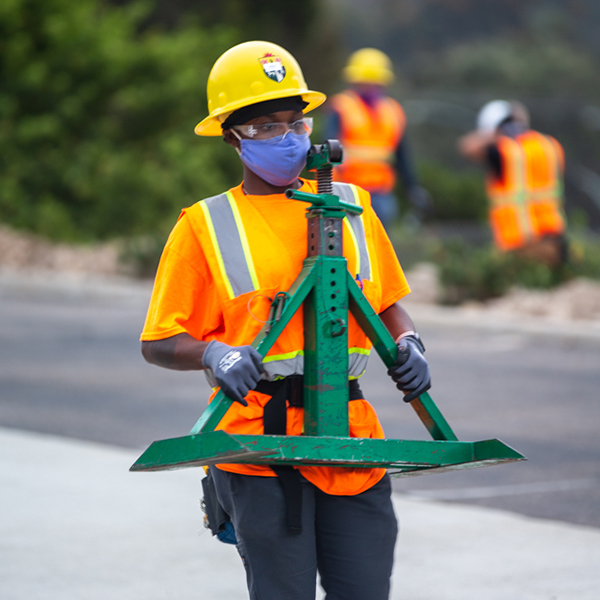 Woman in hard hat carrying equipment