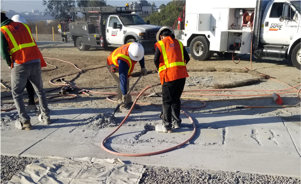 Two students in hard hats working on concrete with SDG&E truck in the background