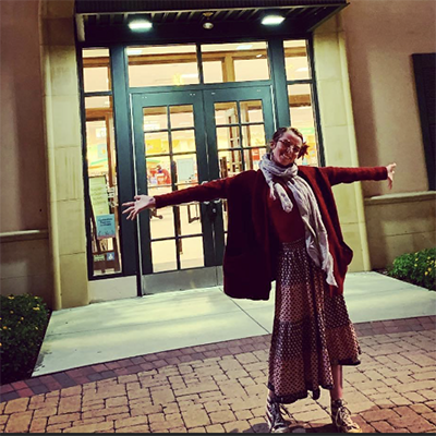 Molly standing in front of Barnes and Noble smiling with her arms spread
