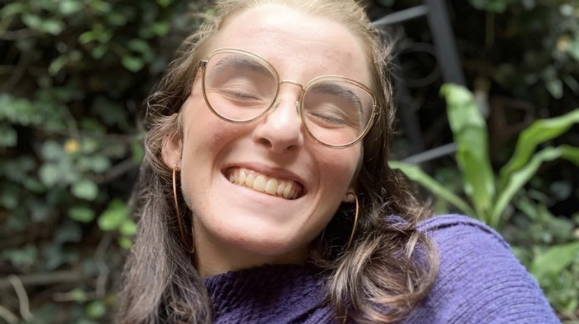 Molly smiling into camera with eyes closed and plants in the background in a purple sweater